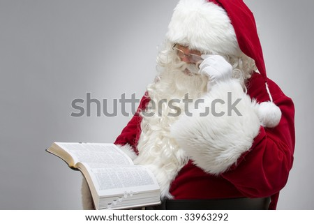 Santa reading from the bible - stock photo