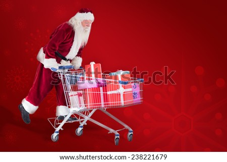 Santa rides on a shopping cart against red background - stock photo