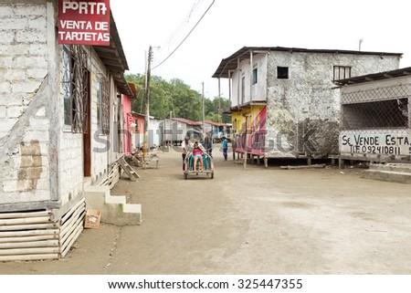 Santa Rosa, Ecuador - 26 July 2015: Two Adult Men Pushing A Disabled Person On Unpaved Road In Santa Rosa On July 26, 2015 - stock photo