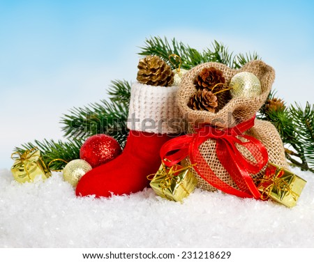 Santa's boot and bag with gifts and cones on snow - stock photo