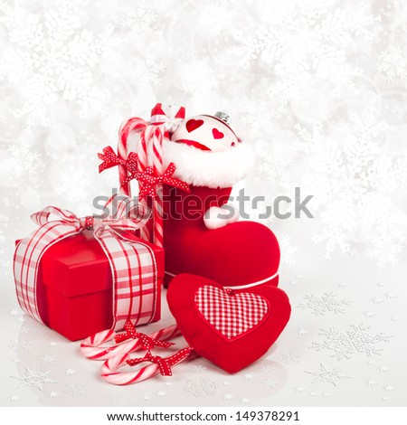 Santa's boot, candy canes and a gift box on abstract winter background - stock photo