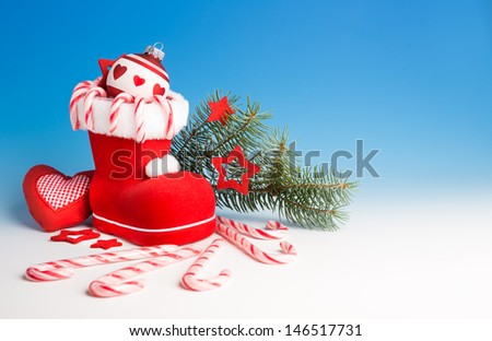 Santa's boot with candy canes and Xmas decorations on blue gradient background, space - stock photo