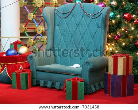 Santa's chair surrounded by presents and christmas tree - stock photo