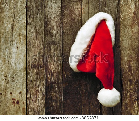 Santa's Christmas hat hanging on a rustic wooden backdrop with copy space. - stock photo
