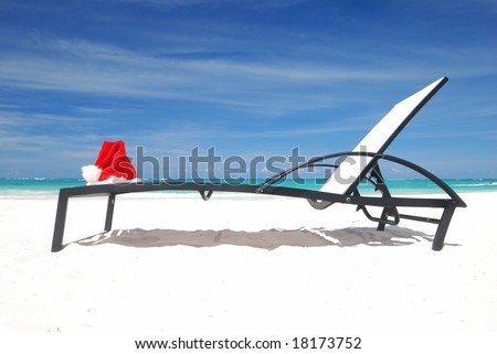 Santa's hat and chaise lounge on the beach - stock photo