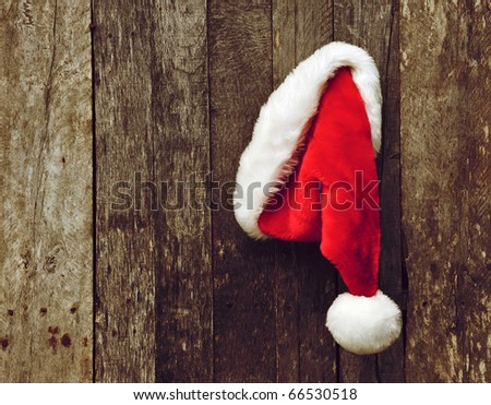 Santa's hat hanging on a rustic wooden backdrop with copy space.