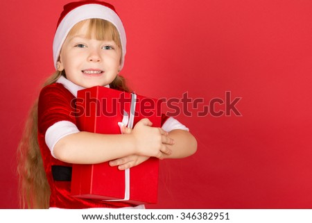 Santaâ??s little helper. Studio portrait of a little cute girl wearing Christmas outfit holding a gift and laughing joyfully against red background copyspace on the side - stock photo