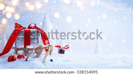 Santa's sleigh with Christmas gifts on the background of snowy trees - stock photo