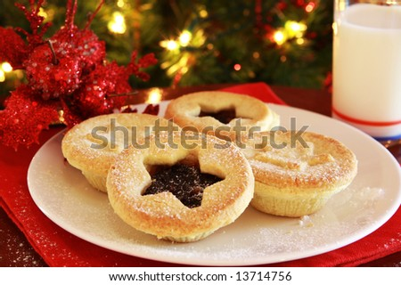 Santa's treats - plate of Christmas mince pies and glass of milk, with Christmas tree behind. - stock photo