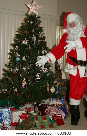 Santa shows off xmas presents - stock photo