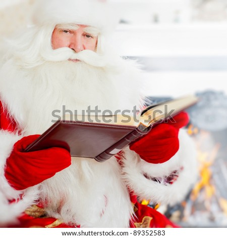 Santa sitting at home and reading a book. Indoors - stock photo