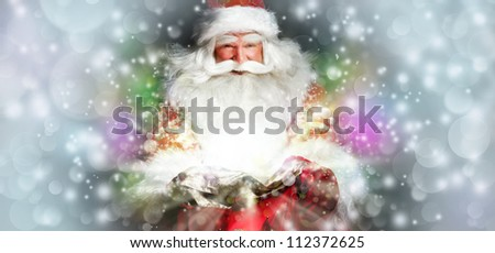 Santa sitting at the Christmas room and looking into the sack - stock photo