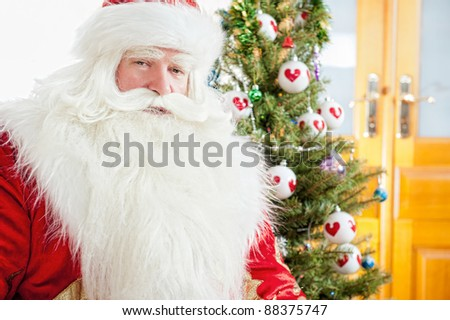 Santa sitting at the Christmas tree, fireplace and looking at camera - stock photo