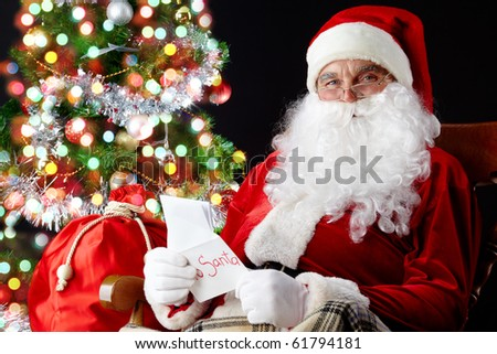 Santa sitting at the Christmas tree, holding Christmas letters and looking at camera