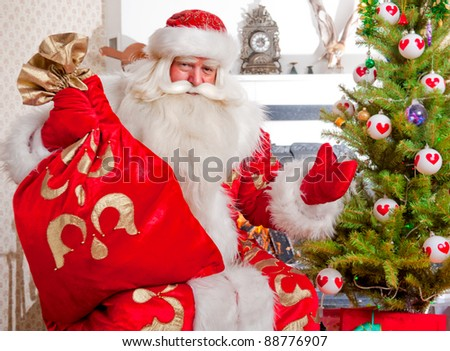 Santa sitting at the Christmas tree, near fireplace and looking at camera. Indoors