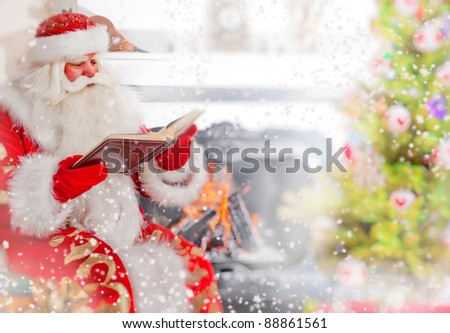 Santa sitting at the Christmas tree, near fireplace and reading a book. Indoors. Magic snowy poster