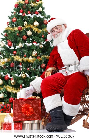 Santa sitting next Christmas tree and taking milk  , that were left  for him - stock photo