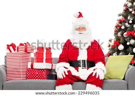 Santa sitting on a sofa by a Christmas tree isolated against white background - stock photo