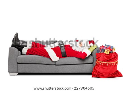 Santa sleeping on sofa with a bag of presents beside him isolated on white background - stock photo
