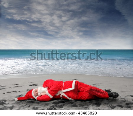 santa sleeping on the beach - stock photo
