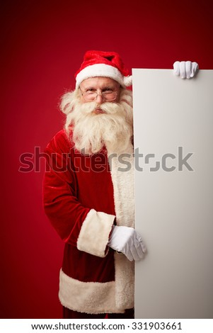 Santa standing by blank paper poster - stock photo
