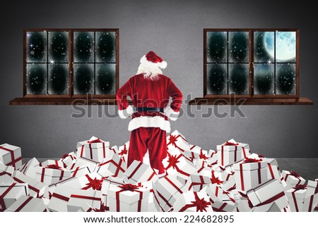 Santa standing on pile of gifts against grey room - stock photo