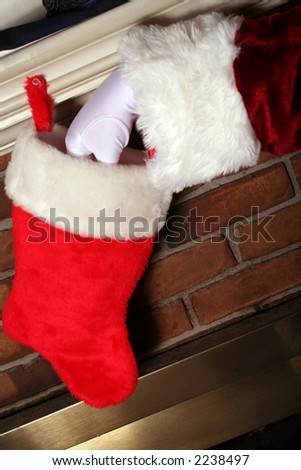 Santa sticking a gift inside a stocking for christmas - stock photo