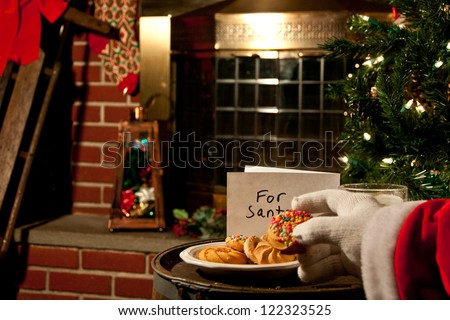 Santa taking a cookie - stock photo