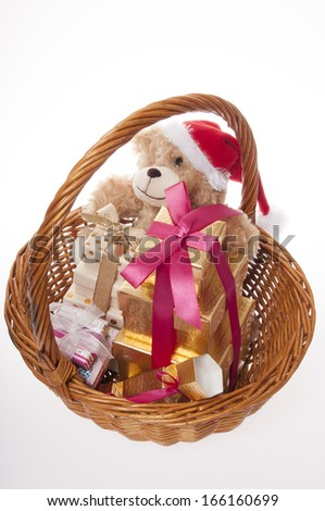 Santa teddy bear in a basket of presents isolated on white background