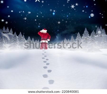 Santa walking in the snow against stars twinkling in night sky - stock photo