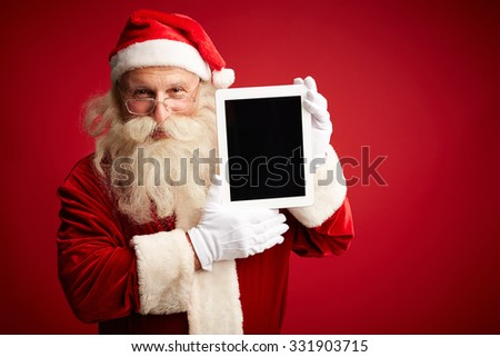 Santa with touchpad looking at camera - stock photo