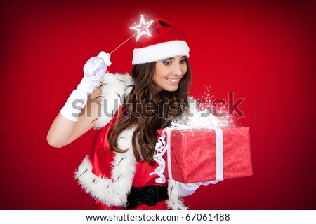 santa woman adding little magic to Christmas present - stock photo