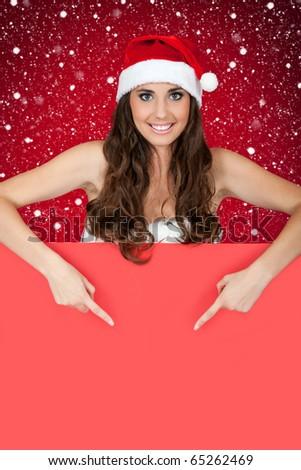 santa woman behind blank board pointing while snowing - stock photo