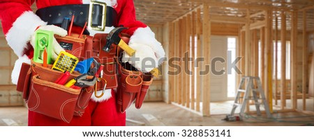 Santa Worker with a tool belt construction background. - stock photo