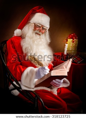 Santa Writes a Magic Feather in the Book by Candlelight - stock photo
