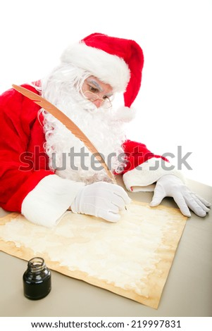 Santa writing his Christmas list on parchment paper with a quill pen and ink.   - stock photo