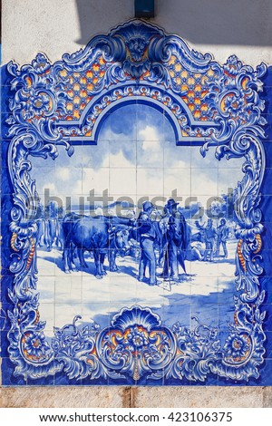 Santarem, Portugal. September 11, 2015: Typical Portuguese Azulejos (Blue tiles) depicting typical regional scenes, in the facade of the 19th century Municipal Market of Santarem, Portugal.  - stock photo