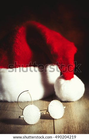 Santas glasses covered in snow with hat in background