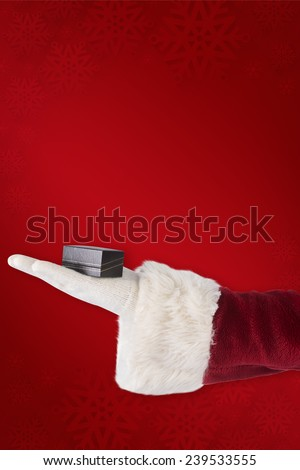 Santas hand shows a small box against red background