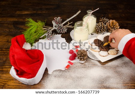 Santas hand taking a cookie next to the wish list