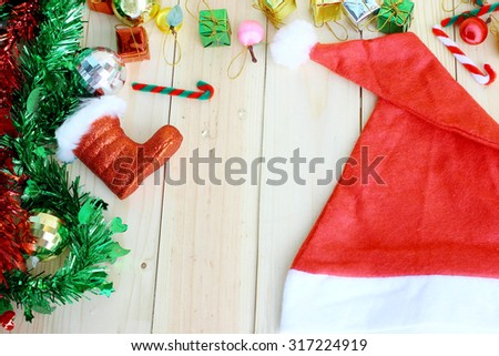 Santas hat and christmas decoration on wood background with space for text