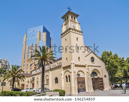 SANTIAGO, CHILE - FEBRUARY 15: Holy Innocents colonial church near a modern building on downtown on February 15, 2011 in Santiago, Chile. Men walking nearby.