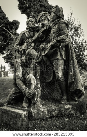 "Santiago de Compostela, Spain - May 9, 2015: Decayed ""tuna singers"" monument, full of moss. The member who is kneeling looks like a skull."