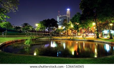 Santipap Park with skyline reflection on the pond at dusk in Bangkok, Thailand - stock photo