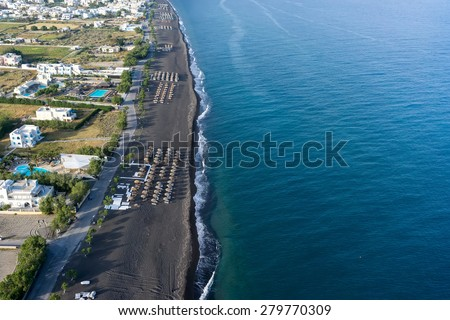 SANTORINI, GREECE - MAY 15,2015: Top view of Perissa beach on the Greek island of Santorini with sunbeds and umbrellas. Beach is covered with fine black sand, and drops off sharply into the water. - stock photo