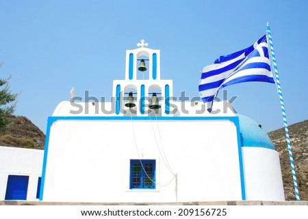 Santorini, Greece: traditional typical white and blue church, with Greek flag and three bells. - stock photo
