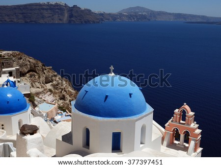 Santorini island in Greece.Oia town on Santorini island, Greece. Traditional and famous houses and churches with blue domes over the Caldera, Aegean sea.