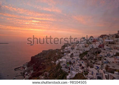 Santorini sunset in Ia village with the ship coming to the island - stock photo