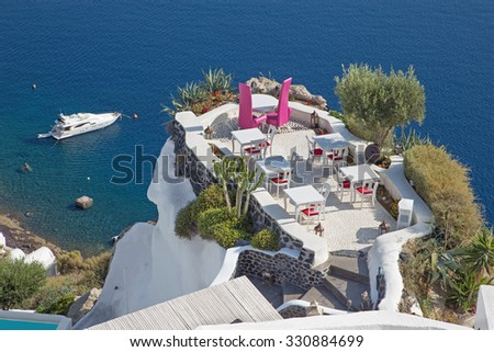Santorini - The restaurant geared to wedding romantic diner in Oia (Ia) and the yacht under cliffs in the background. - stock photo