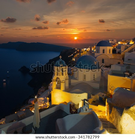 Santorini - The sunset over the blue churchs cupolas in Oia and the Therasia island in the background.   - stock photo
